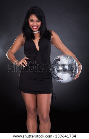 Young Woman Holding Disco Ball Over Black Background - stock photo