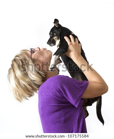 Young woman holding dog above head - stock photo