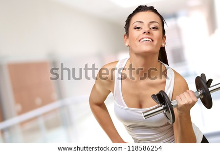 Young woman holding dumbells, indoor - stock photo