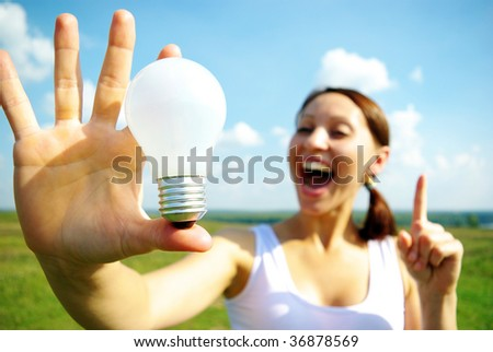 Young woman holding  electric bulb in hand. - stock photo