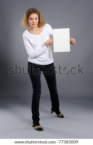 young woman holding empty white board, on a  grey background