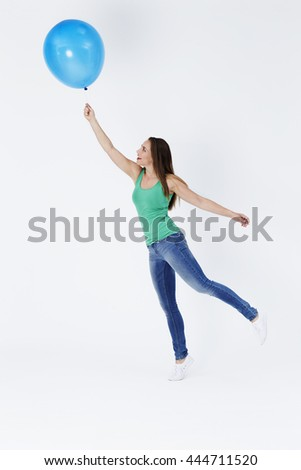 Young woman holding floating balloon, studio