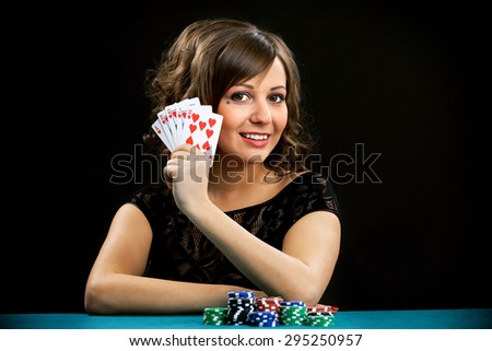 Young woman holding gambling chips on black background
