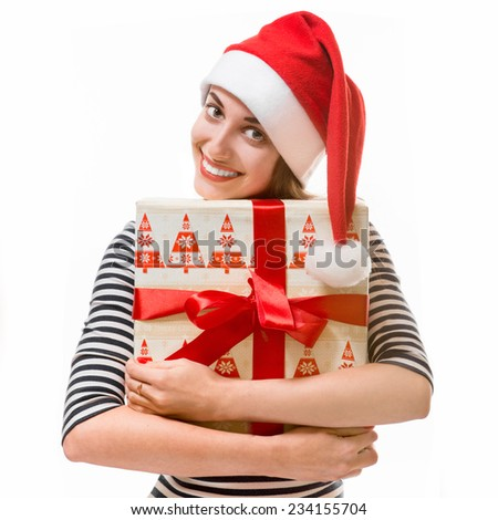 Young woman holding gifts dressed in striped dress and Christmas hat isolated on white background - stock photo