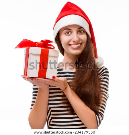 Young woman holding giftt dressed in striped dress and Christmas hat isolated on white background - stock photo