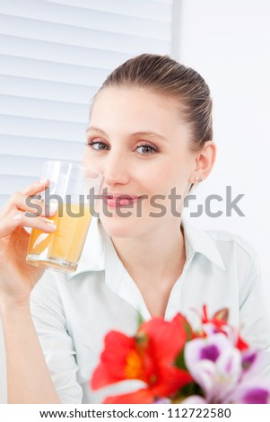Young woman holding glass of juice.