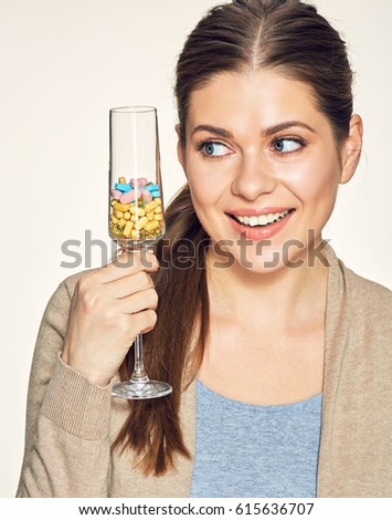 Young woman holding glass with vitamin pills. Isolated portrait.