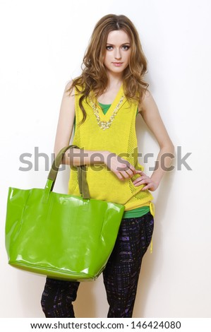 young woman holding green bag posing white background - stock photo