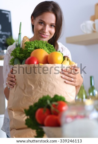 Young woman holding grocery shopping bag with vegetables and fruit