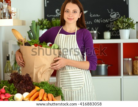 Young woman holding grocery shopping bag with vegetables Standing in the kitchen - stock photo