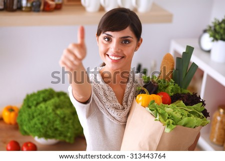 Young woman holding grocery shopping bag with vegetables Standing in the kitchen and showing ok - stock photo