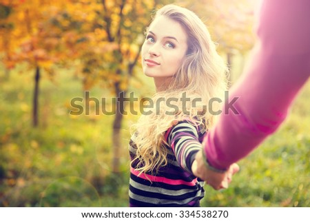 Young Woman Holding Hands on Autumn Background in Sunny Day. Toned Photo with Lens Flare Effect and Copy Space.  - stock photo