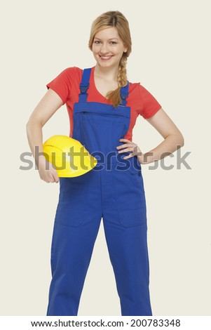 Young woman holding hardhat smiling - stock photo