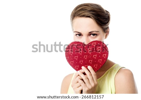 Young woman holding heart shape gift box