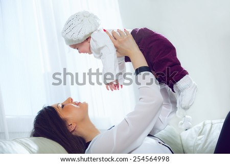 Young woman holding her baby in her arms in the living room - stock photo