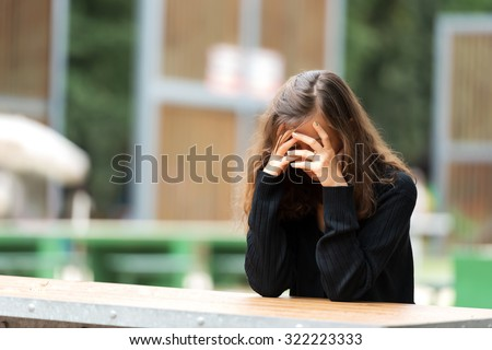 Young woman holding her head in shame.