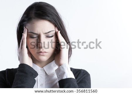 Young woman holding her head.Migraine and headache problem.Overworked,stressed woman.Menstrual and period pain.Intensive lifestyle and fast life. - stock photo