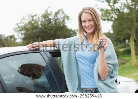 Young woman holding her key beside of her car - stock photo