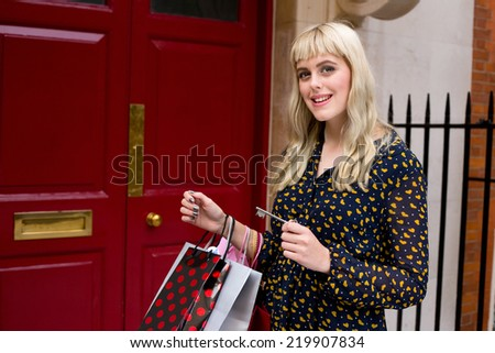 young woman holding her key to enter her house.