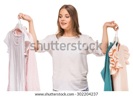 Young woman holding her new dresses on white background.
