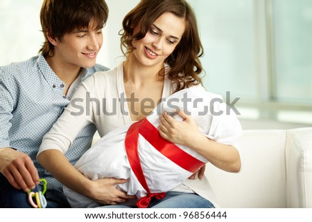 Young woman holding her newborn baby in, her husband smiling happily