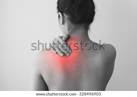 Young woman holding her shoulder in pain, isolated on white background, focus on pain area
