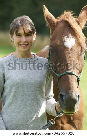 Young Woman Holding Horse In Field