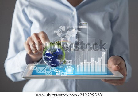 Young woman holding in her hand a tablet pc and touching the earth globe Elements of this image furnished by NASA - stock photo