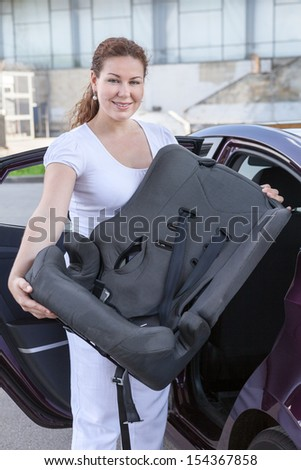Young woman holding infant safety seat standing near car