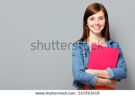 Young woman holding job application on grey background - stock photo