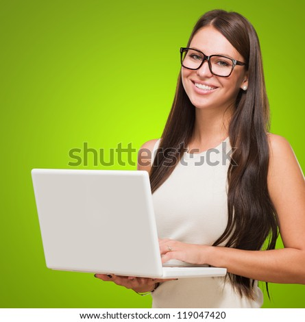 Young Woman Holding Laptop against a green background - stock photo