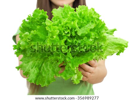 Young woman holding lettuce, green salad over white background