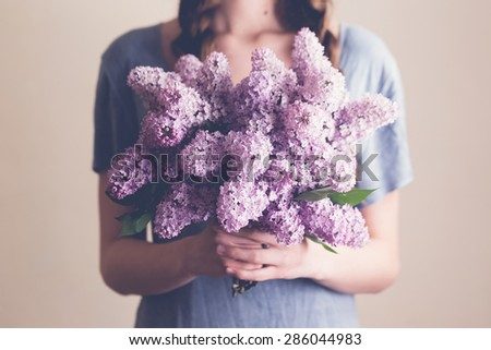 Young woman holding lilac flowers