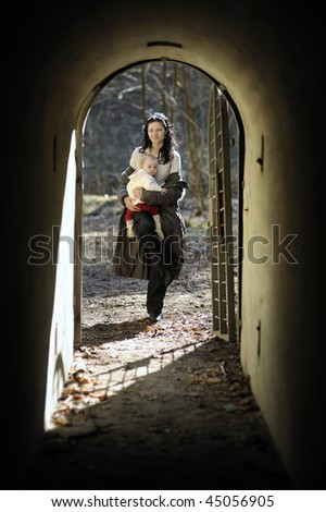 Young woman holding little baby girl in a tunnel