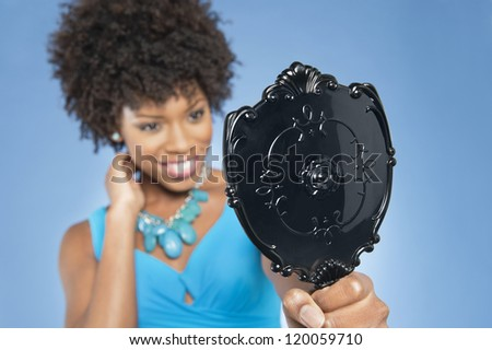 Young woman holding looking at mirror over colored background - stock photo