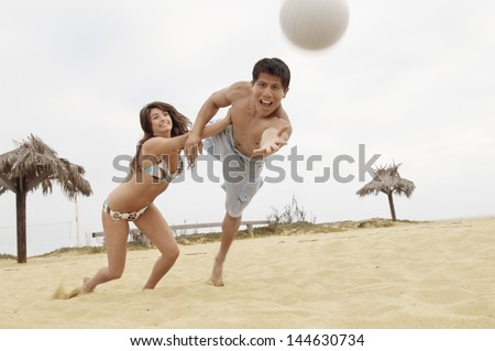 Young woman holding man back from diving for volleyball on the beach - stock photo