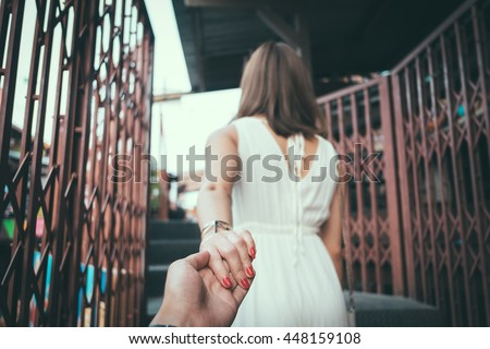 Young woman holding man hand. soft-focus on hand, vintage style processed.