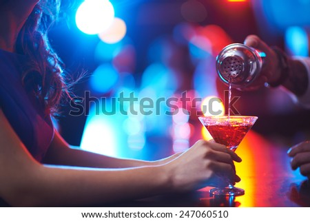 Young woman holding martini glass while barman pouring cocktail - stock photo