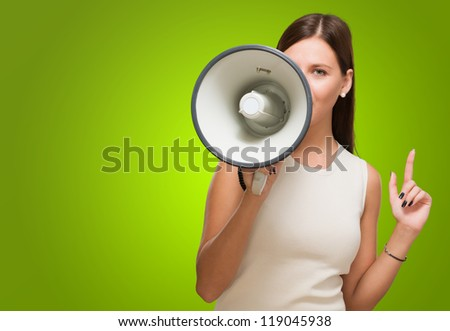 Young Woman Holding Megaphone against a green background - stock photo