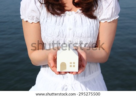 young woman holding miniature house - stock photo