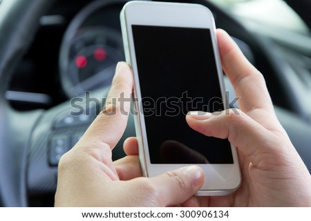 Young woman holding mobile device in the car  - stock photo