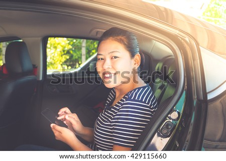 Young woman holding mobile device sitting in the car on back seats - vintage style color effect (face focused) - stock photo