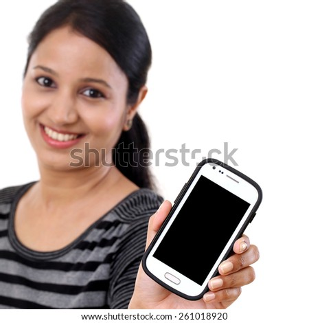 Young woman holding mobile phone against white background - stock photo