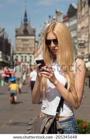 Young woman holding mobile phone in hands on the street