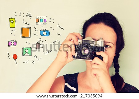 young woman holding old camera and varius colorful sketches as her imagination - stock photo