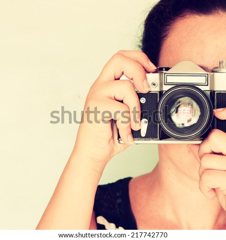 young woman holding old camera. vintage effect - stock photo