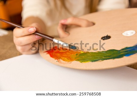 Young woman holding paintbrush and choosing paint on pallet - stock photo