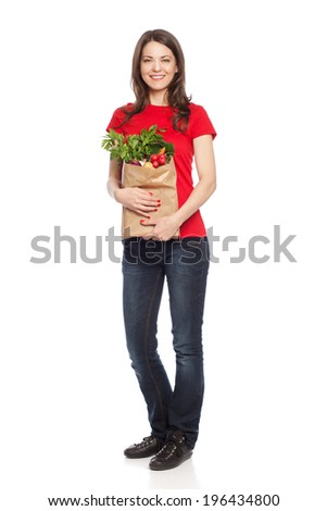 Young woman holding paper bag full of groceries, isolated on white