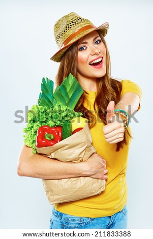 Young woman holding paper bag with vegetarian food. Diet concept. White background. Thumb up.