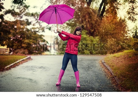 Young woman holding pink umbrella in a park - stock photo